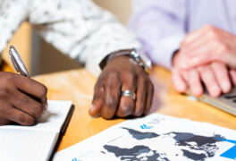 Close up detail of black business man signing documents with caucasian colleague in background.